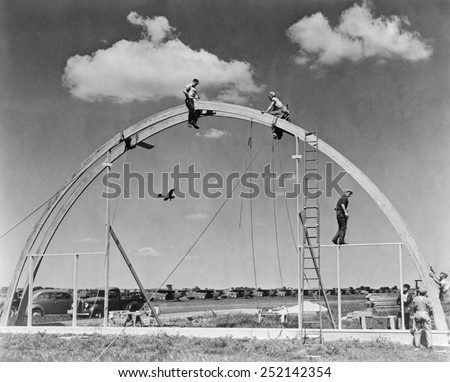 Construction workers on airplane hangar with prefabricated 'Rilco' glued laminated wooden arches. The arch of the Morey Airplane Hangar has a span of 70 feet. Janesville, Wisconsin, ca. 1942.