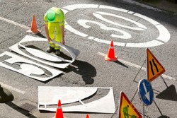 construction workers painting in highway the signal of 30 or 50  limit speed  in city  road