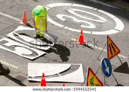 construction workers painting in highway the signal of 30 or 50  limit speed  in city  road Foto stock ©
