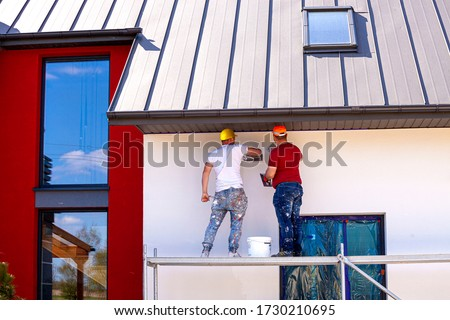 Construction workers plaster the facade of the house. Application Of Facade Plaster.