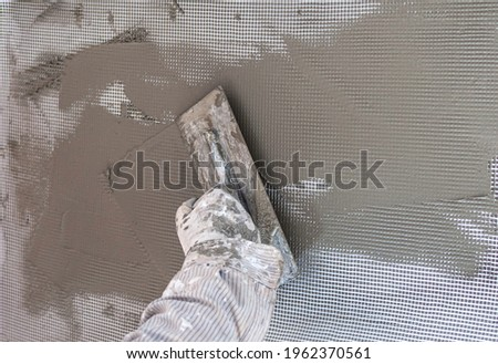 Construction workers plaster the facade of the house. Worker plastering tool plaster marble on interior plaster rough