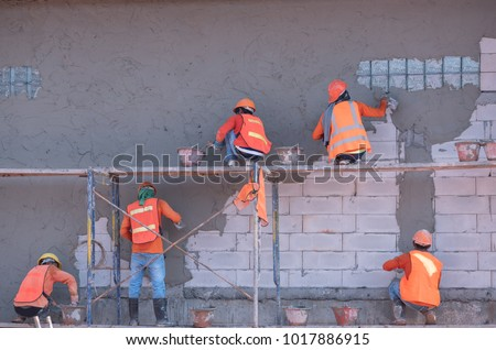 construction workers plastering building wall and beam using cement plaster mix of cement and sand at the construction site