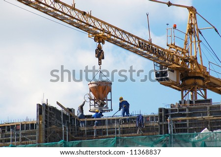 Construction workers pouring concrete mix from charging hopper transported by jib crane