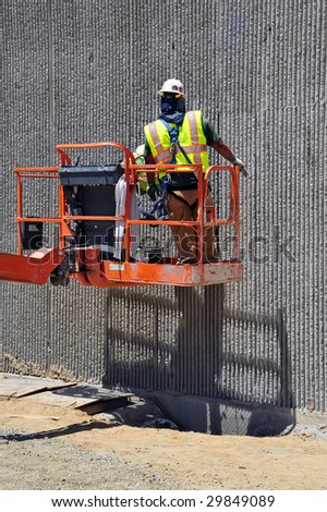 Construction workers use chemicals to strip away form residue on decorative concrete retaining wall