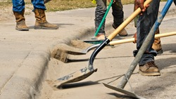 Construction workers use shovels and broom to clean dirt off the street by the sidewalk at a work site. Closeup of boots, shovels, dirt, and curb.