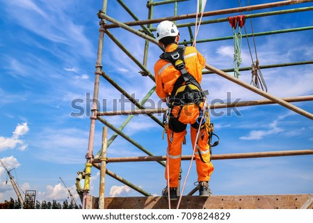 construction workers wearing safety harness belt during training at high place