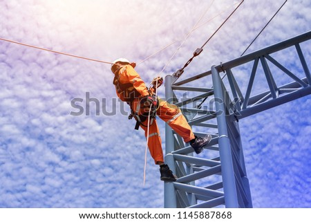Construction workers wearing safety harness belt during training at high place, Construction workers tying  on road construction structure with on blue sky background  stock photo
