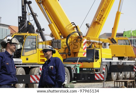 construction workers with giant mobile cranes in background