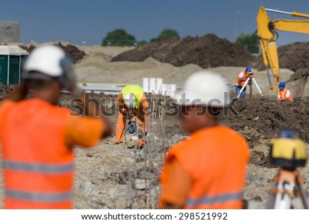 Construction workers working on different jobs at building site