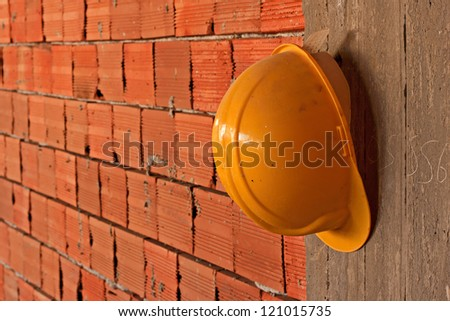 Construction workers yellow hard hat hanging on concrete wall - stock photo