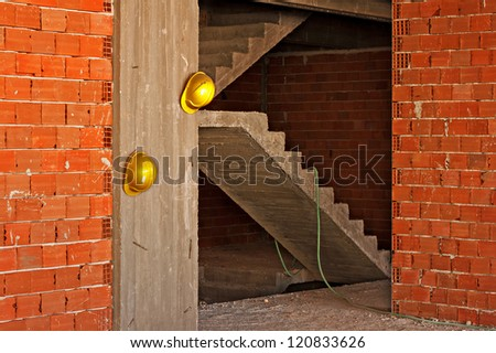 Construction workers yellow hard hats hanging on concrete wall