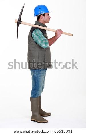 Construction working holding a pickaxe - stock photo