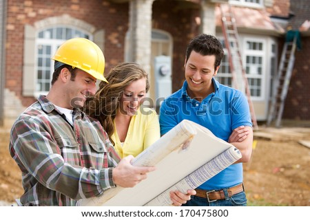 Construction: Young Couple Look At Home Plans with Builder.