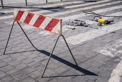 Construction zone or roadworks warning sign ahed on city street. A stone was removed from a pedestrian crossing with electric rotary hammer drill. Close-up.