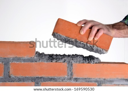 Constructor hand holding a brick and building a wall.building brick block wall