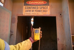 Constructor worker hand holding gas test leak detector device while commencing safety gas testing atmosphere at main entry and exit on confined space door prior to work construction site, Australia