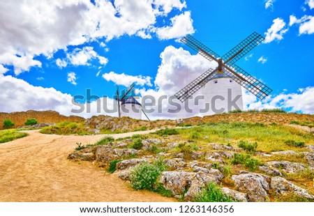 Consuegra, Spain. Wind mills at knolls, Toledo region, Castilla La Mancha, Spain. Route of Don Quixote with windmills. Summer landscape with blue sky and clouds.