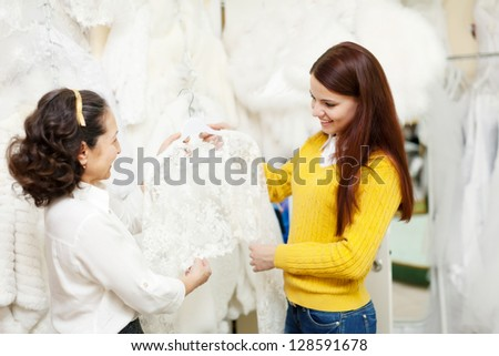 consultant helps bride chooses bridal clothes at shop of wedding fashion. Focus on girl