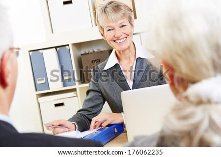 Consultant in bank giving financial advice zu senior couple