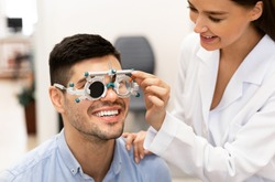 Consultation With The Ophthalmologist Concept. Portrait of woman optometrist examining eyesight of male client with trial frame and closed eye. Woman doing checkup of man's eye with diagnostic tool