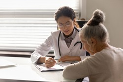 Consulting patient. Capable young latin woman doc counsel female retiree prescribe treatment explain therapy details. Old lady sign informed consent on surgical procedure at attending physician office