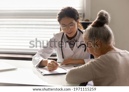 Consulting patient. Capable young latin woman doc counsel female retiree prescribe treatment explain therapy details. Old lady sign informed consent on surgical procedure at attending physician office Photo stock ©