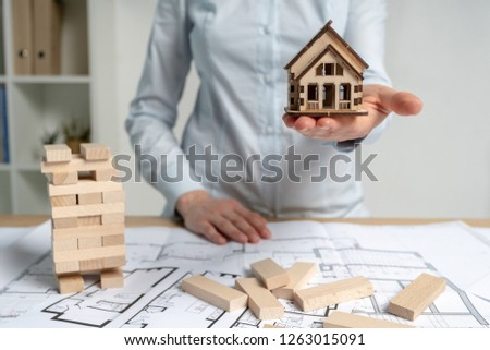 Consumer and consumerism concept. Businesswoman in her formal wear standing indoor light workplace office. She holding little house object in hand making opportunity for rental flat or apartment