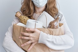 Consumer buying panic about coronavirus covid-19 concept. People buy essentials in bulk at supermarkets concept. Woman hold shopping bag with rolls of toilet paper, pasta and buckweat