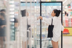 Consumer goods shopping buy supermarket refrigerator, The girl is opening the fridge to buy chilled products in the supermarket in the mall. , Consumers choose fresh and quality products
