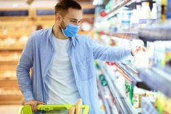 Consumerism And Consumption. Male customer in medical face mask choosing dairy products, taking bottle of milk or yoghurt from the fridge. Man standing with shopping trolley near freezer in mall