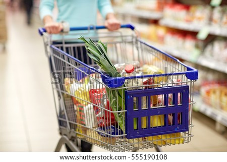 consumerism and people concept - woman with shopping cart or trolley buying food at grocery store or supermarket