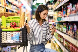 Consumption And Consumerism. Portrait Of Young Woman With Shopping Cart In Market Buying Groceries Food Taking Products From Shelves In Store, Holding Glass Jar Of Sauce, Checking Label Or Expiry Date