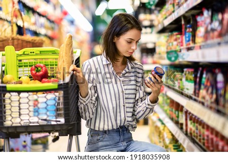 Consumption And Consumerism. Portrait Of Young Woman With Shopping Cart In Market Buying Groceries Food Taking Products From Shelves In Store, Holding Glass Jar Of Sauce, Checking Label Or Expiry Date Сток-фото ©