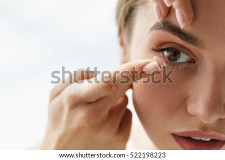 Photo of  Contact Lens For Vision. Closeup Of Female Face With Applying Contact Lens On Her Brown Eyes. Beautiful Woman Putting Eye Lenses With Hands. Opthalmology Medicine And Health. High Resolution