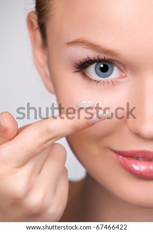contact lens on finger of young woman looking on camera; closeup portrait