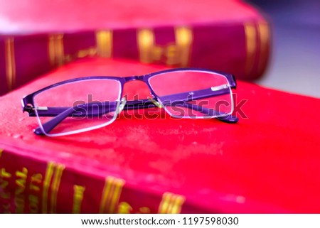 CONTACT LENSE ON RED LAW BOOKS INDICATING EDUCATION OF LAW . LAW BOOKS , CONTACT LENSE, STUDY OF LAW WITH CONTACT LENSES.
