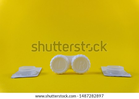 Contact lenses and lens storage case on yellow background