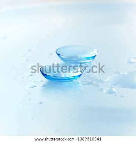 Contact lenses and water drops on light blue background. Eyewear, eyesight and vision, eye care and health, ophthalmology and optometry concept, close up, selective focus