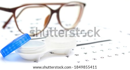 Contact lenses case and eye glasses on and eye test chart. Vision concept. Way to improve vision Foto stock ©