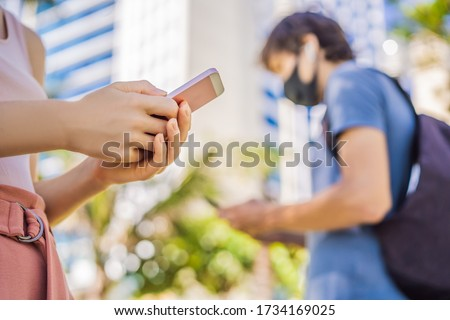 contact tracing app COVID-19 Pandemic Coronavirus Mobile Application - people Wearing Face Mask Using Smart Phone App in City Street to Aid Contact Tracing in Response to the 2019-20 Coronavirus