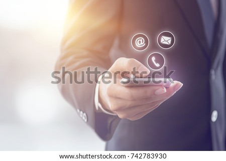 CONTACT US, Hand of Businessman holding mobile smartphone with ( mail,phone,email ) icon. cutomer support concept, copy space.