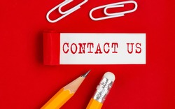 CONTACT US message written under torn red paper with pencils and clips, business
