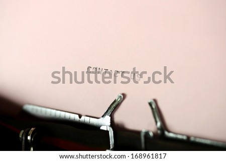 Contact us typing type on purple paper on typewriter