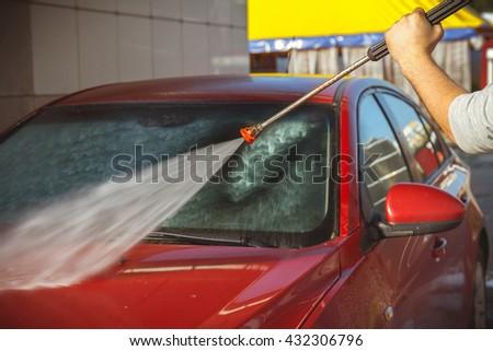 Contactless car wash self-service. Young man washing his car #432306796