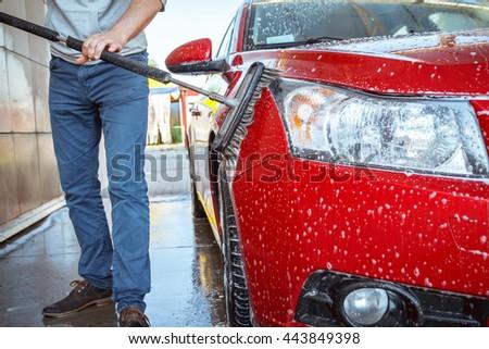 Contactless car wash self-service. Young man washing his car #443849398