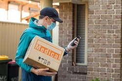 Contactless delivery during COVID-19 pandemic lockdown concept. Courier wearing mask and gloves holds a parcel with medical equipment and checking address details on the smartphone