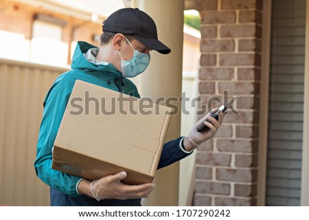 Contactless delivery during COVID-19 pandemic lockdown concept. Courier wearing mask and gloves holds a parcel box and checking address details on the smartphone