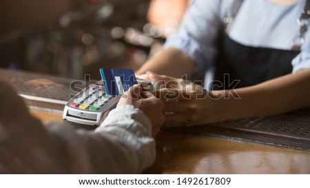 Contactless payment concept, female customer holding credit card near nfc technology on counter, client make transaction pay bill on terminal rfid cashier machine in restaurant store, close up view
