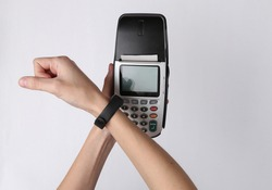 Contactless payment. Hand with smart bracelet pays payment terminal on white background
