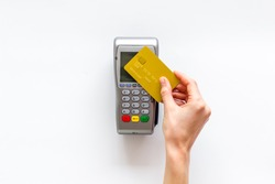 Contactless payment, paypass. Hand hold bank card near terminal on white background top-down
